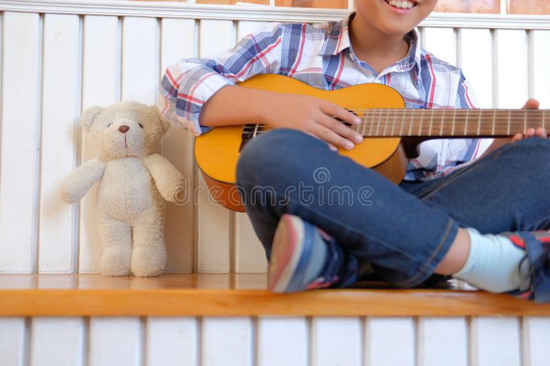 asian kid boy child playing guitar ukulele. children leisure act stock images