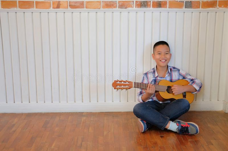 asian kid boy child playing guitar ukulele. children leisure act stock photography