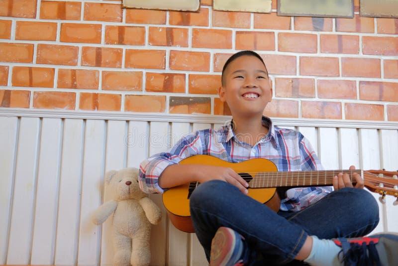 asian kid boy child playing guitar ukulele. children leisure act stock photos