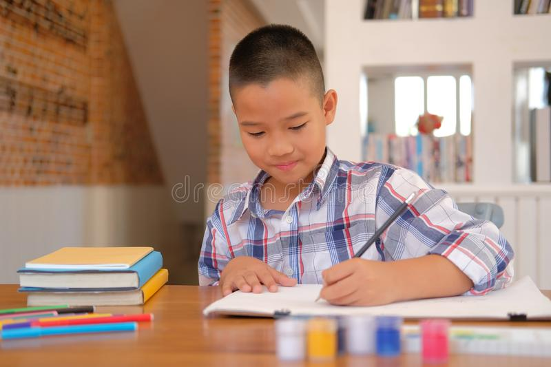 asian kid boy child schoolboy drawing picture. children activity stock photo