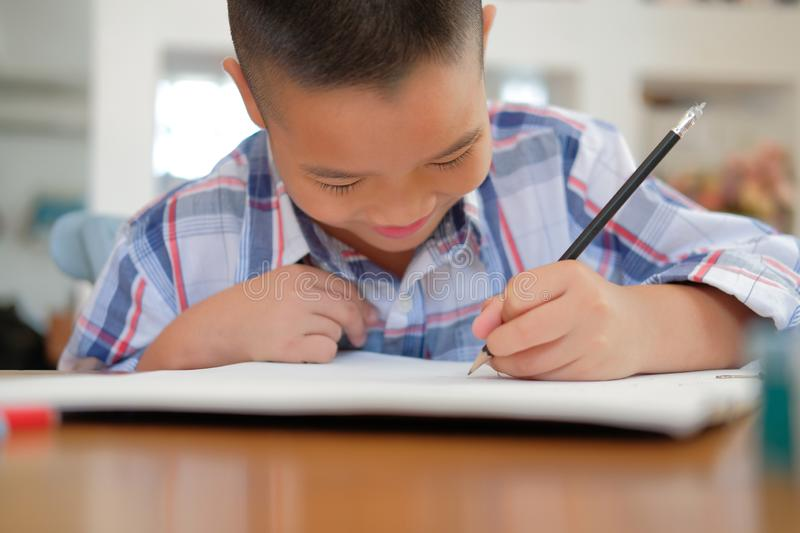 asian kid boy child schoolboy drawing picture. children activity stock photos