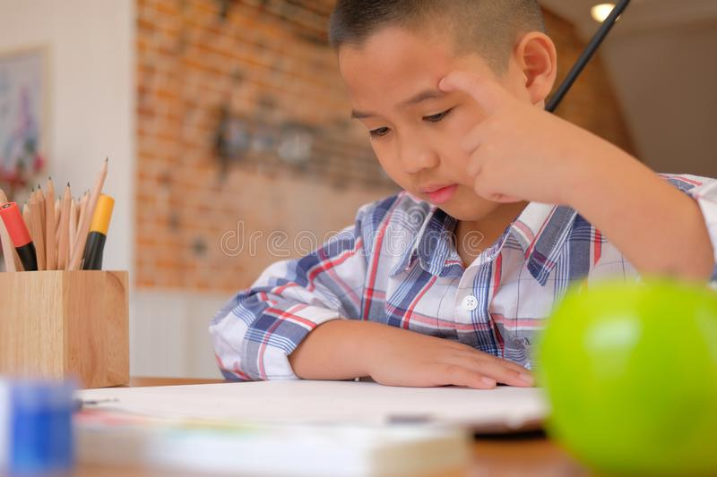 asian kid boy child schoolboy thinking while drawing picture. ch royalty free stock images