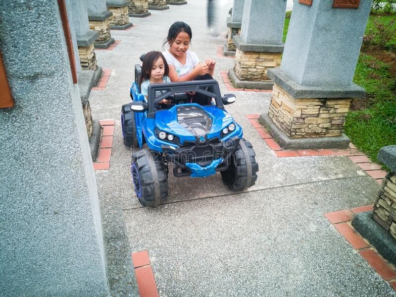 An Asian kid driving electric toy car in a tropical park. Outdoor toys. Children in battery power vehicle. stock photos