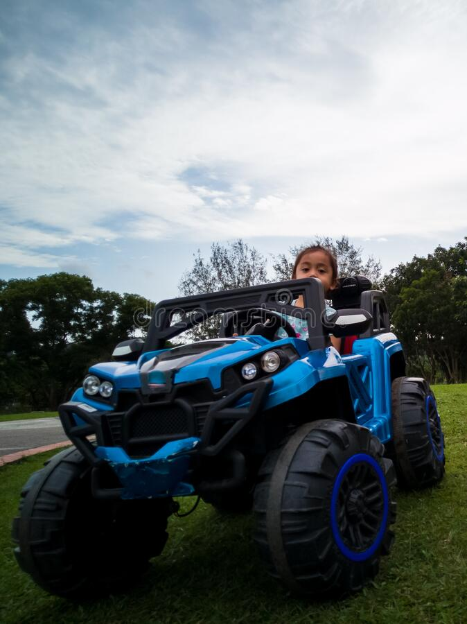 An Asian kid driving electric toy car in a tropical park. Outdoor toys. Children in battery power vehicle. Little girl riding. stock photography