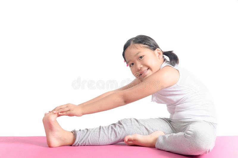 Asian kid exercise on yoga mat isolated royalty free stock images