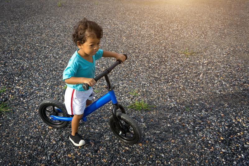 Asian kid first day play balance bike. royalty free stock photos