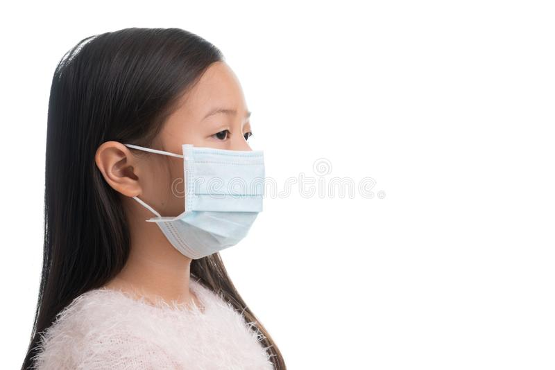 Asian kid girl age 7 years with protection mask against flu virus. Or air polution isolated on white royalty free stock photo