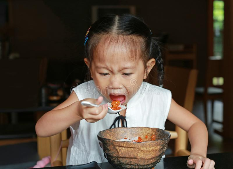Asian kid girl eating delicious food on table for lunch in the restaurant.  stock images