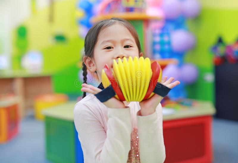 Asian kid girl having fun with Toys, musical instruments.  stock image