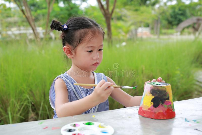 Asian kid girl paint on earthenware dish stock photography