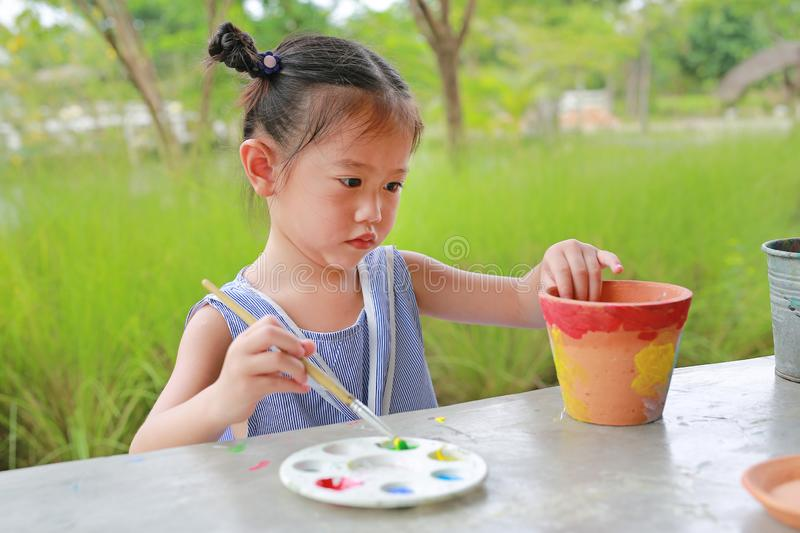 Asian kid girl paint on earthenware dish.  stock images