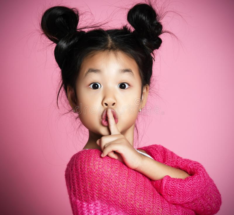 Asian kid girl in pink sweater shows shh sign Close up portrait. Asian kid girl in pink sweater shows shh sign on pink background. Close up portrait stock photography