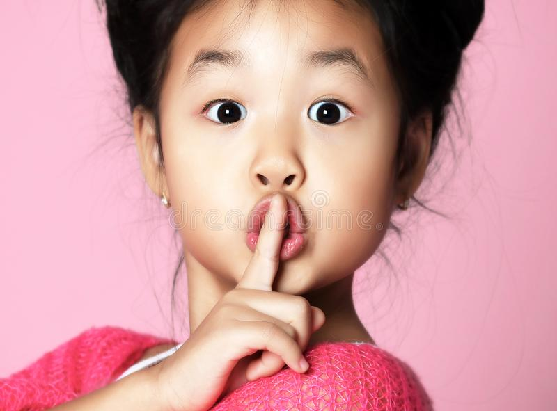 Asian kid girl in pink sweater shows shhh quiet sign on pink. Background royalty free stock photo