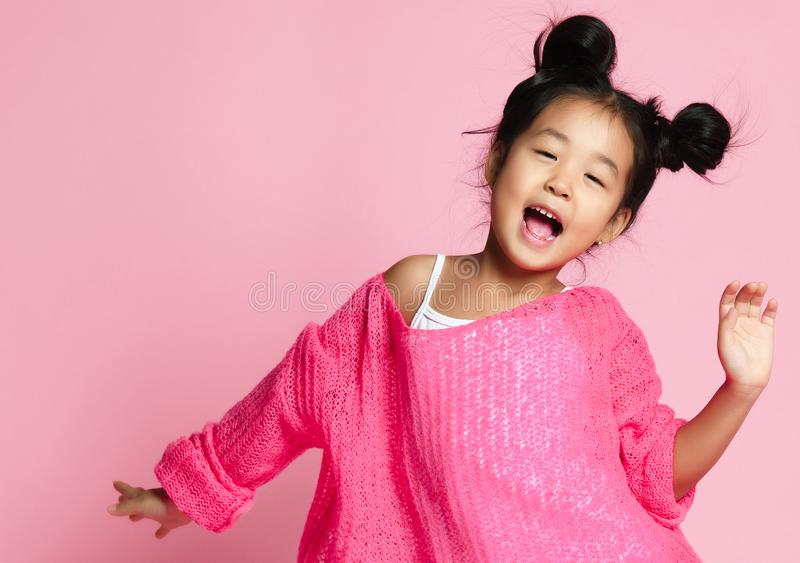 Asian kid girl in pink sweater, white pants and funny buns sings. close up. Asian kid girl in pink sweater, white pants and funny buns sings on pink background stock image
