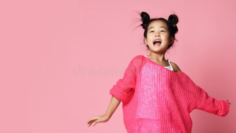 Asian kid girl in pink sweater, white pants and funny buns sings happy smiling stock image