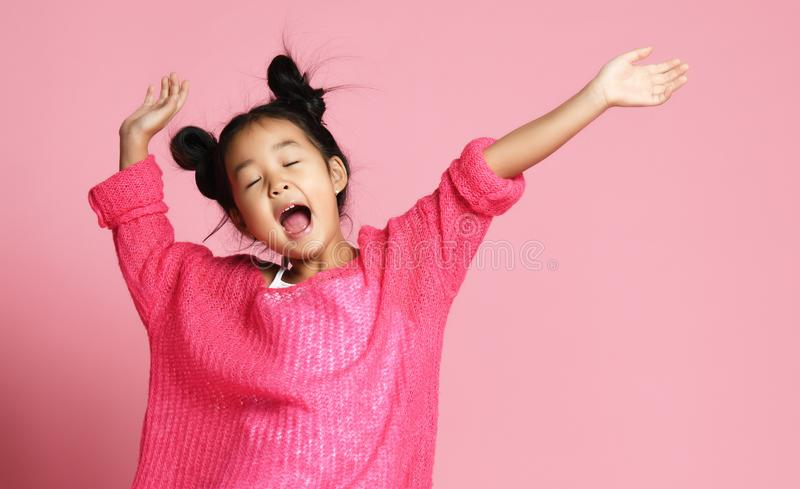 Asian kid girl in pink sweater, white pants and funny buns sings singing dancing on pink. Background royalty free stock photography