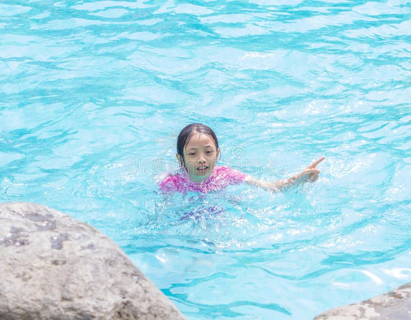 Asian Kid Girl in Swimming Pool with Finger Pointing royalty free stock photography