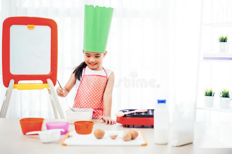 Asian kid having fun with cooking and preparing the dough, bake cookies in the kitchen.  royalty free stock photo