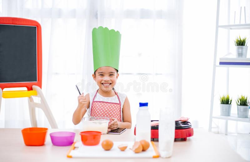 Asian kid having fun with cooking and preparing the dough, bake cookies in the kitchen.  stock images