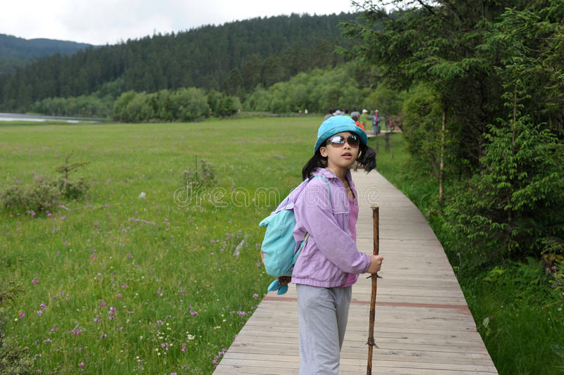 Asian kid hiking. On the plank road in the park stock photo