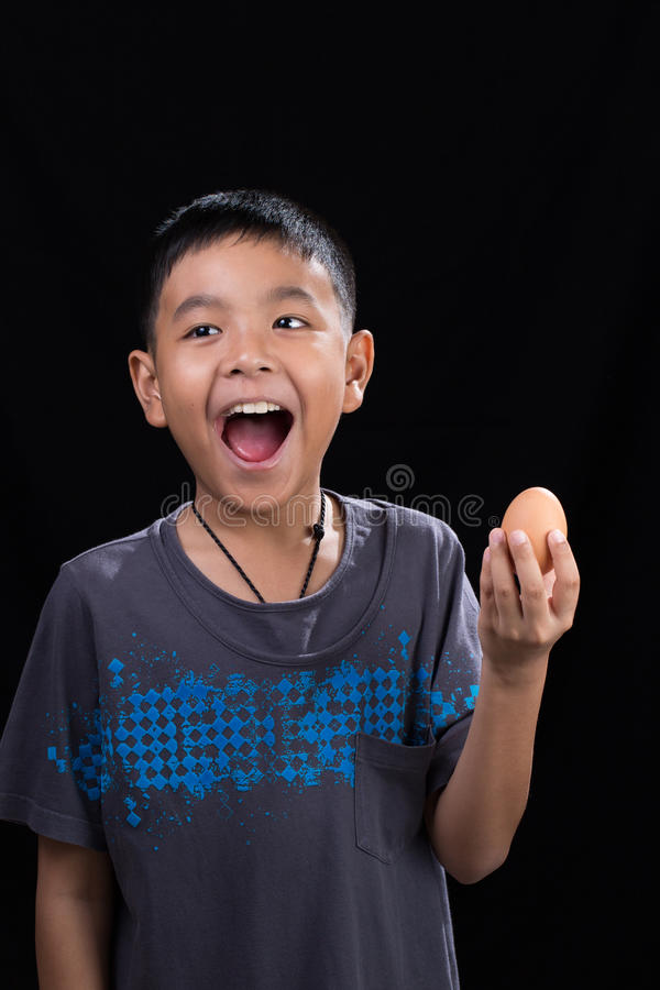 Asian kid holding egg in his hand on black background stock photography