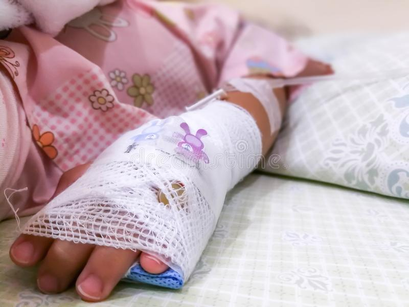 Asian kid patient, Close up of iv plug in patient`s child hand.heparin lock in hospital with saline intravenous IV drip royalty free stock images