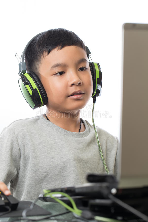 Asian kid play computer games (vertical shot). Asian kid play computer internet games and wear headset to communicate royalty free stock photos