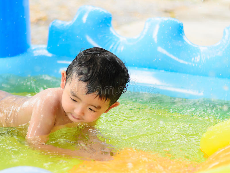Asian kid playing in inflatable baby swimming pool on hot summer. Asian kid playing in inflatable baby pool. Boy swim and splash in colorful swimming pool with royalty free stock photo