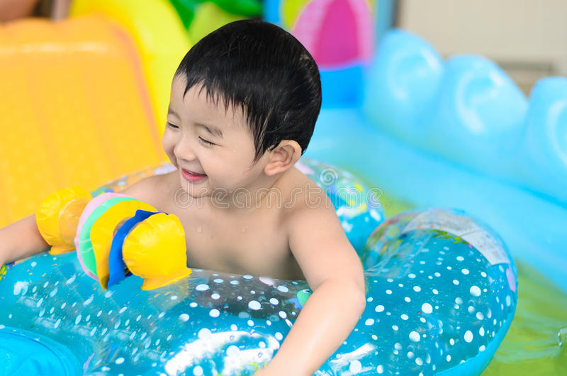 Asian kid playing in inflatable baby swimming pool on hot summer. Asian kid playing in inflatable baby pool. Boy swim and splash in colorful swimming pool with stock photos