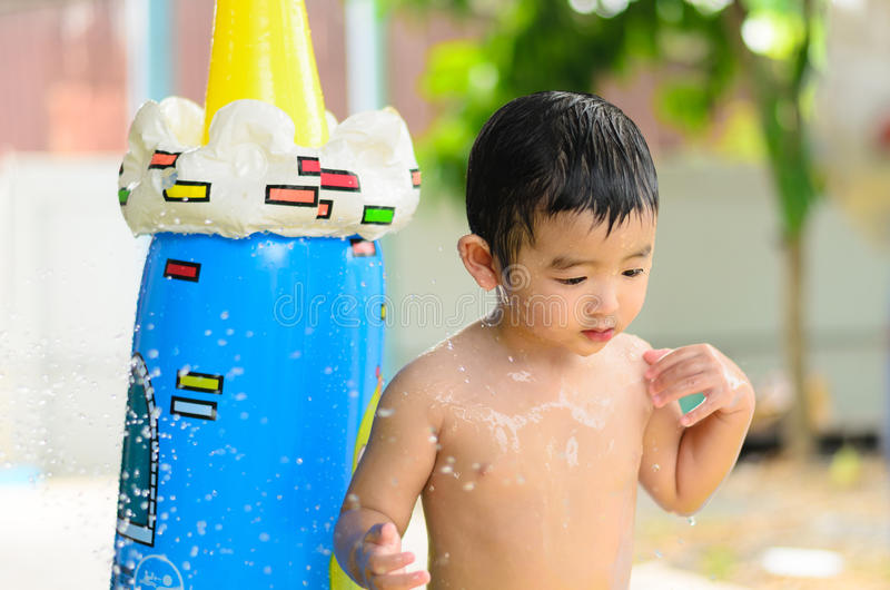 Asian kid playing in inflatable baby swimming pool on hot summer. Asian kid playing in inflatable baby pool. Boy swim and splash in colorful swimming pool with royalty free stock image