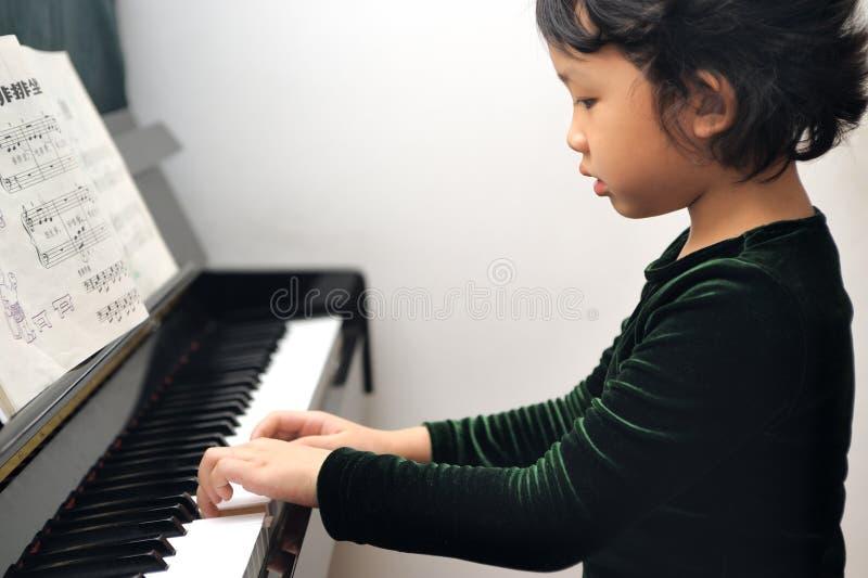 Asian kid playing piano royalty free stock photo