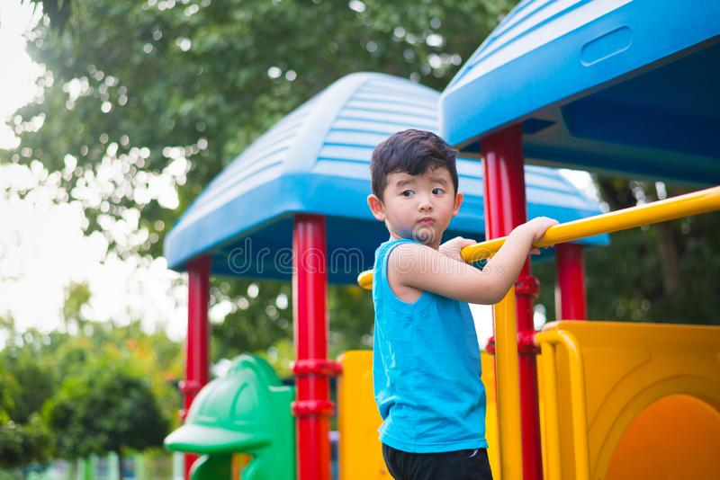 Asian kid playing at the playground under the sunlight in summer, Happy kid in kindergarten or preschool school yard royalty free stock image