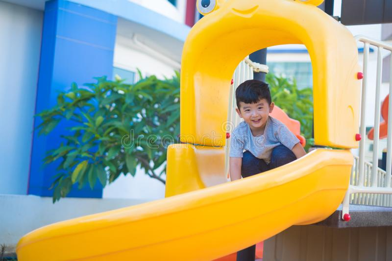 Asian kid playing slide at the playground under the sunlight in summer, Happy kid in kindergarten stock photos