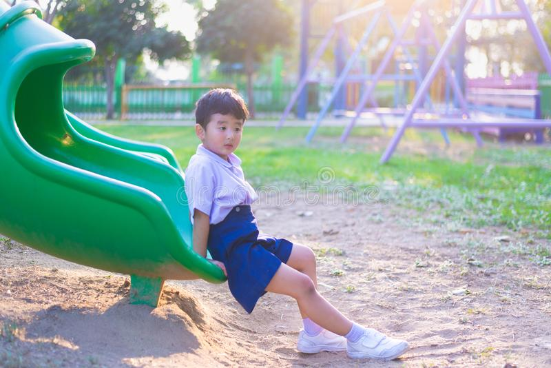 Asian kid playing slide at the playground under the sunlight in summer, Happy kid in kindergarten royalty free stock photography