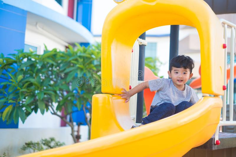 Asian kid playing slide at the playground under the sunlight in summer, Happy kid in kindergarten or preschool school yard royalty free stock photography