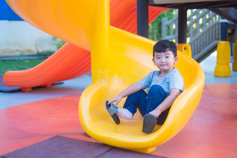 Asian kid playing slide at the playground under the sunlight in summer, Happy kid in kindergarten or preschool school yard royalty free stock image