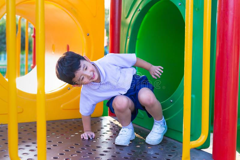 Asian kid playing slide at the playground under the sunlight in summer, Happy kid in kindergarten stock photo