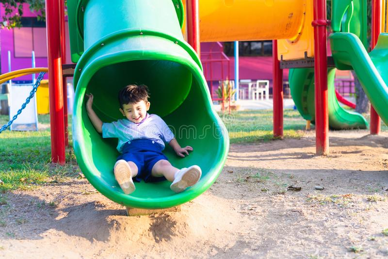 Asian kid playing slide at the playground under the sunlight in summer, Happy kid in kindergarten royalty free stock photos