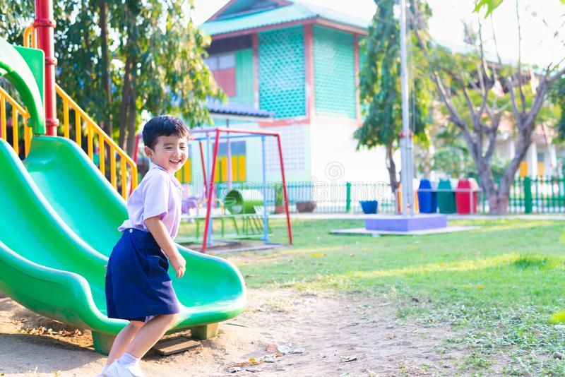 Asian kid playing slide at the playground under the sunlight in summer, Happy kid in kindergarten stock images