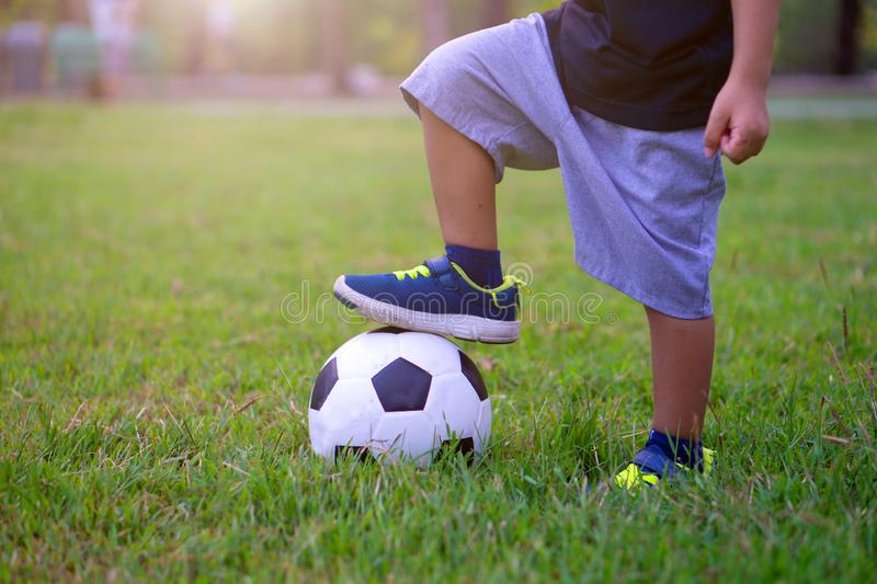 Asian kid playing soccer or football in the park. Step on the ball.  royalty free stock photography