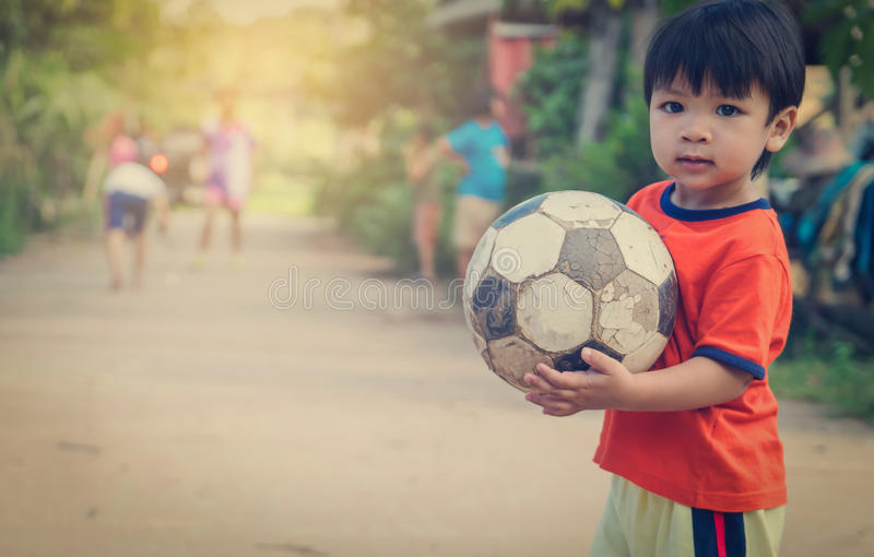 Asian kid in poor village playing with soccer ball stock image