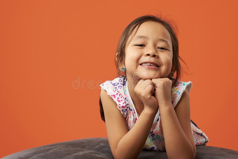 Asian kid posing on a beanbag royalty free stock photography
