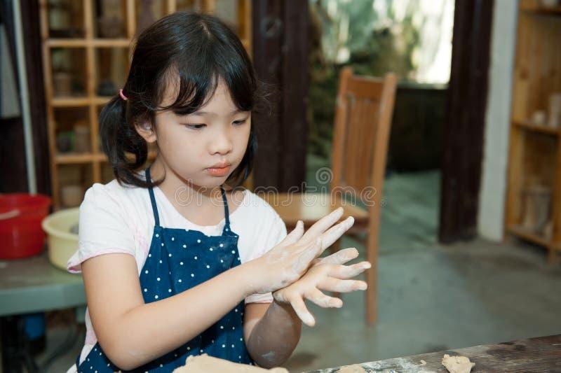 Asian kid shaping pottery royalty free stock image
