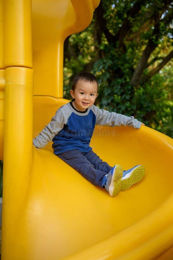 Asian kid on slide stock images