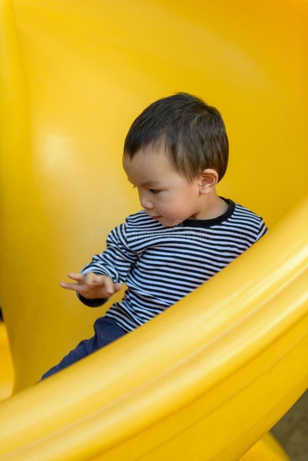Asian kid on slide stock image