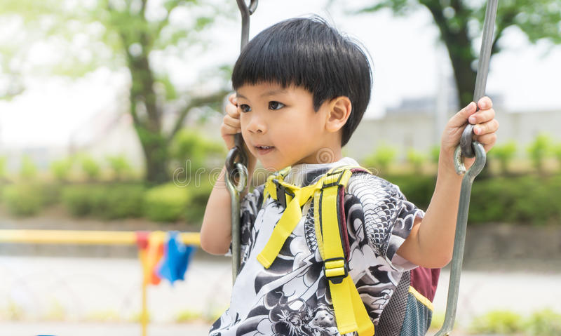 Asian kid is swaying on a swing. Asian kid is swaying on a playground swing royalty free stock photography