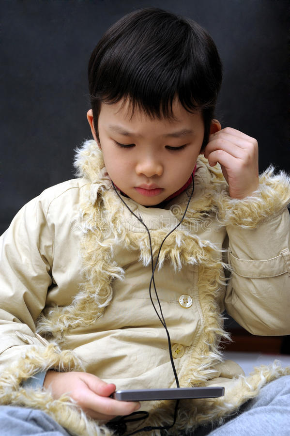 Asian kid with video player stock photo