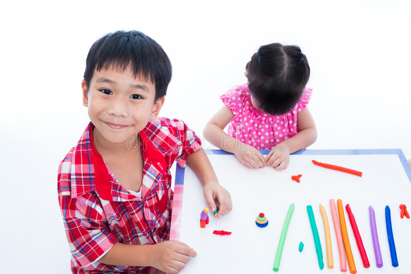 Asian kids playing with play clay on table. Strengthen the imagination royalty free stock photography