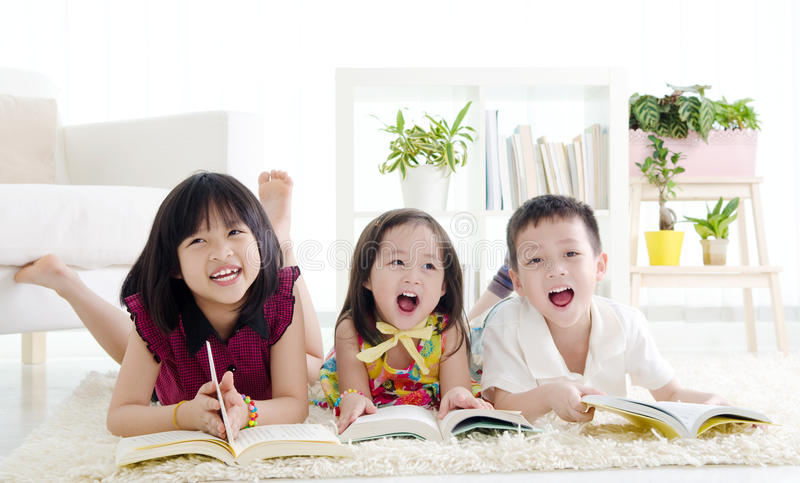 Asian kids. Putting books on their head royalty free stock photography