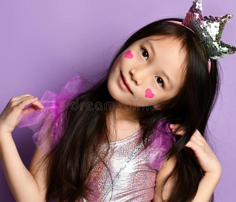 Asian Korean kid girl princess in crown closeup portrait Happy smiling laughing with a painted red hearts sign on cheeks royalty free stock photography